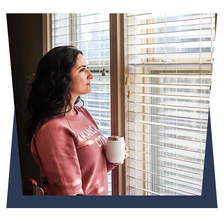 Lady with a coffe infront of window